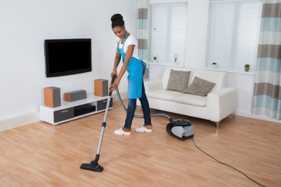 female caregiver cleaning living room