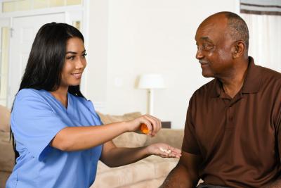 female caregiver helping senior woman for medication intake