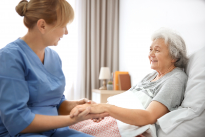 female caregiver holding the hand of senior woman